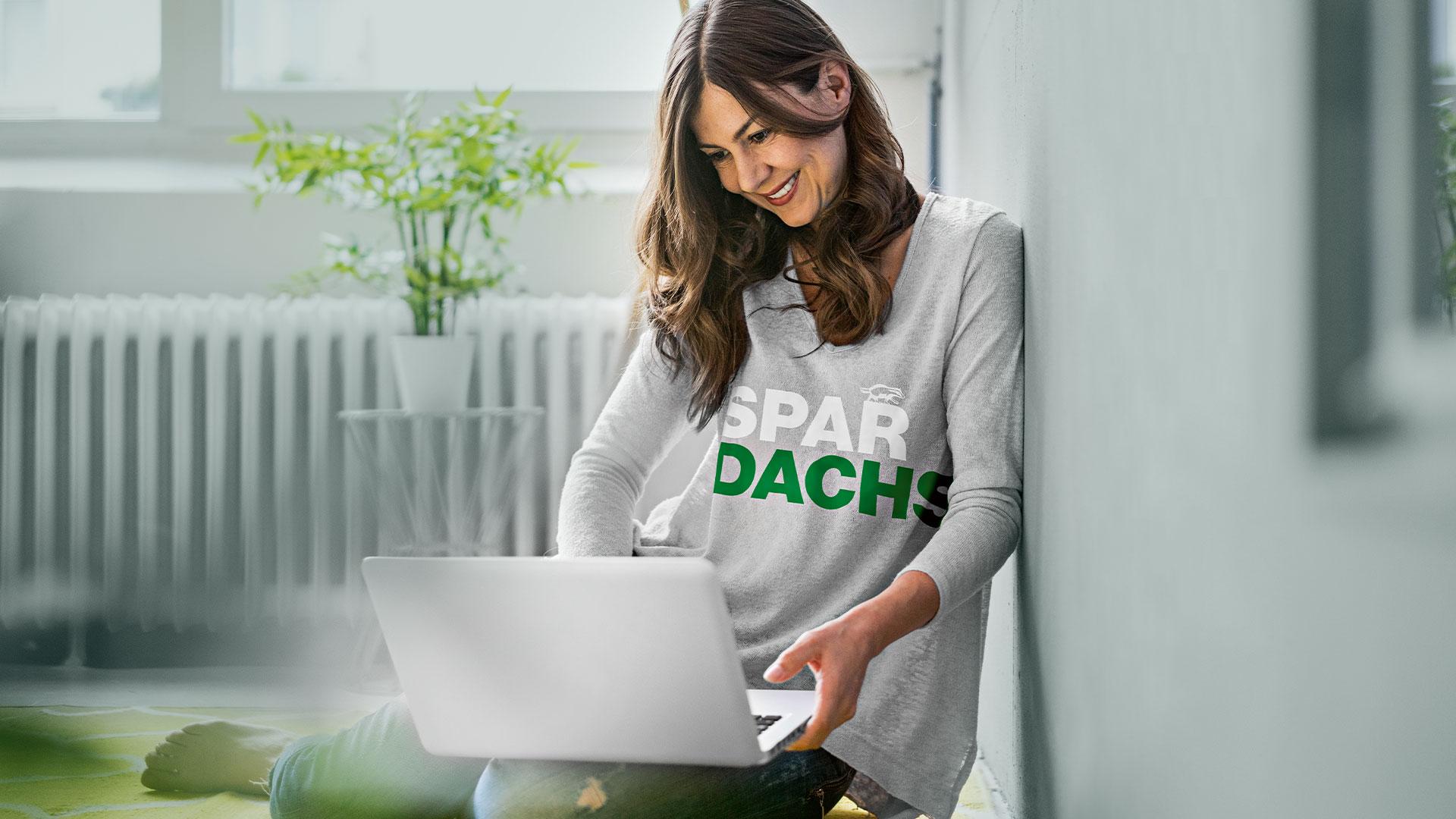 """Eine Frau sitzt mit ihrem Laptop auf dem Boden und trägt ein Oberteil mit der Aufschrift """"Spar Dachs""""."""