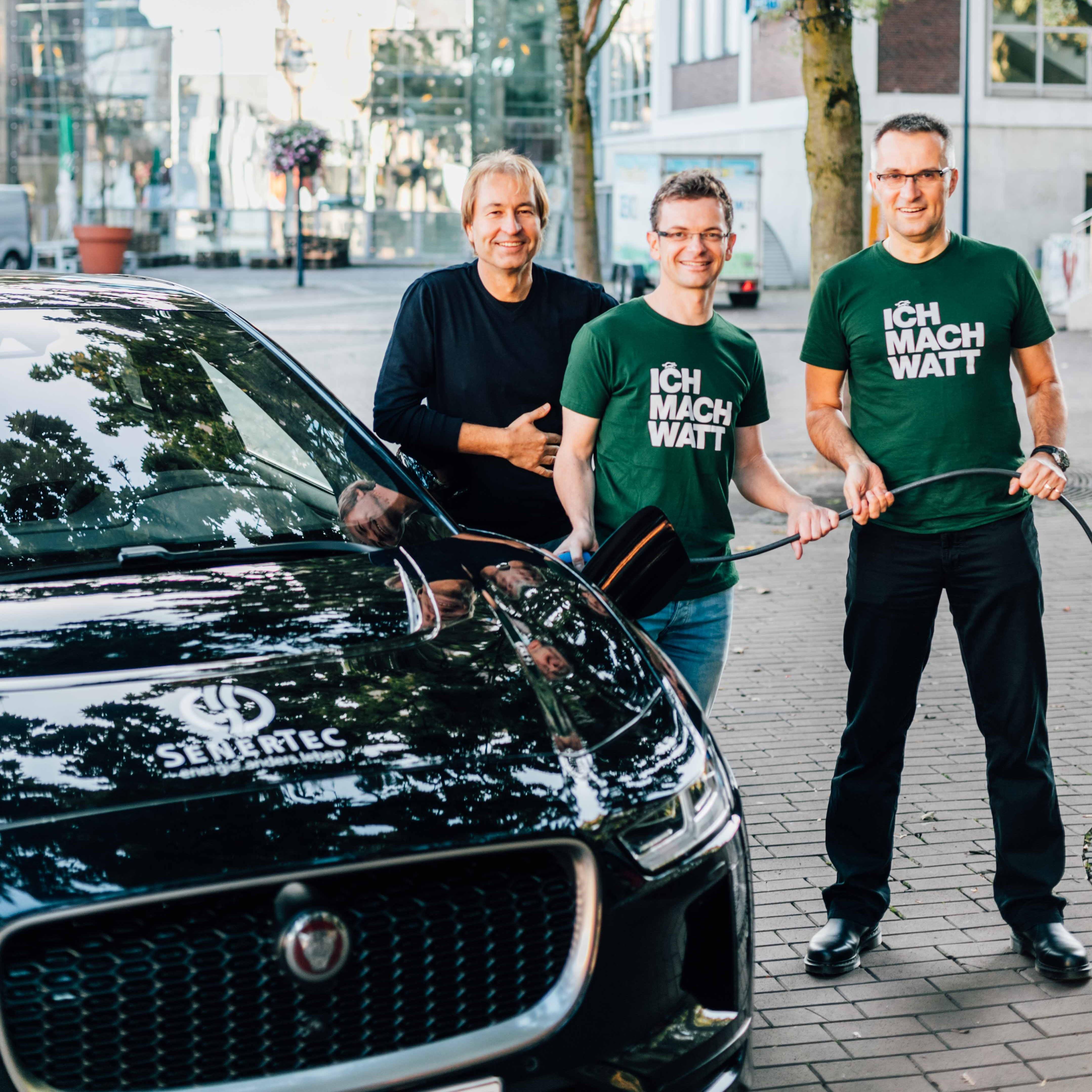 Das Team SenerTec steht mit Ladekabel neben dem E-Auto Jaguar I-PACE mit SenerTec-Branding.