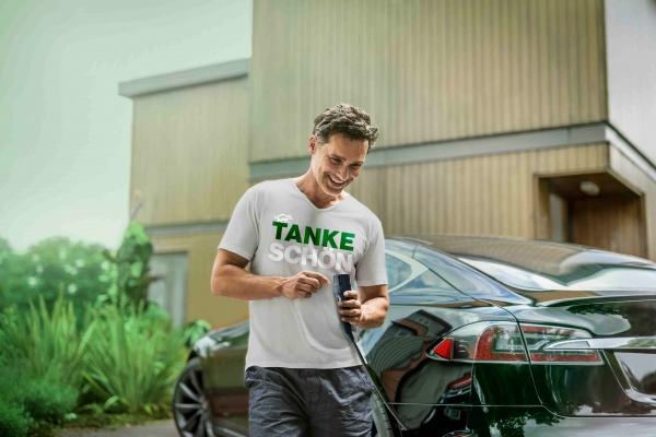 Portrait eines Mannes, der ein E-Auto lädt und ein SenerTec-Shirt trägt.