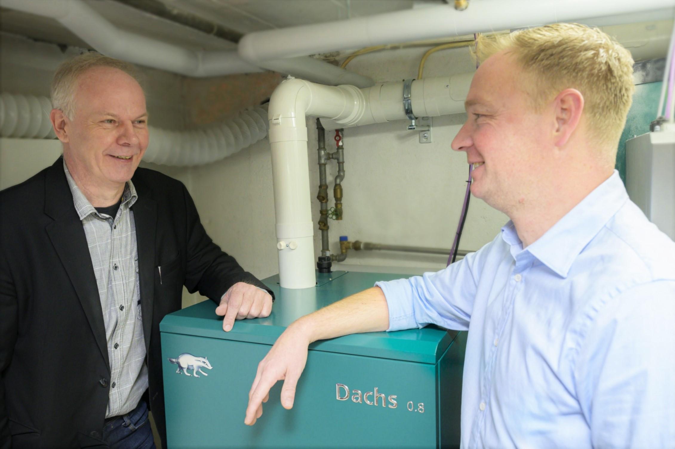 Der Besitzer Herr Fröhlich steht mit Center-Geschäftsführer Peter Löser im Keller bei seinem neuen Dachs 0.8 mit Brennstoffzelle.
