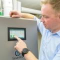 Der Dachs 0.8 mit Brennstoffzellentechnologie. Herr Fröhlich, Besitzer des Dachs 0.8, bedient das Display seiner neuen stromerzeugenden Heizung.
